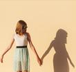 Leinwandbild Motiv the girl holds the hand of her shadow