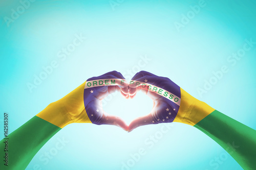 Photo  Brazil flag on people hands in heart shape for labor day and national holiday ce