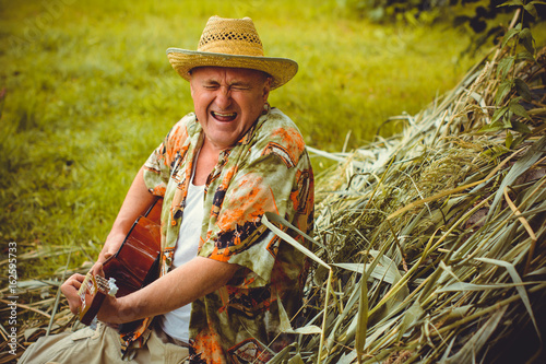Funny older man in print shirt tourist playing guitar and sing song on nature ou Canvas Print