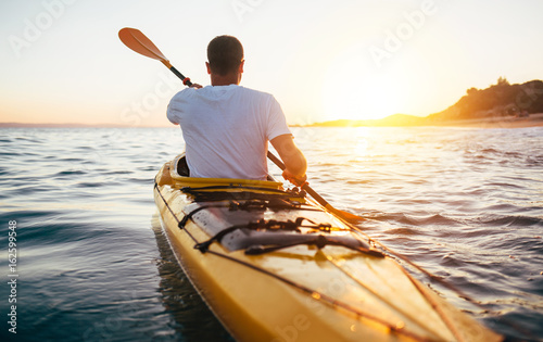 Rear view of kayaker man paddle kayak at sunset sea