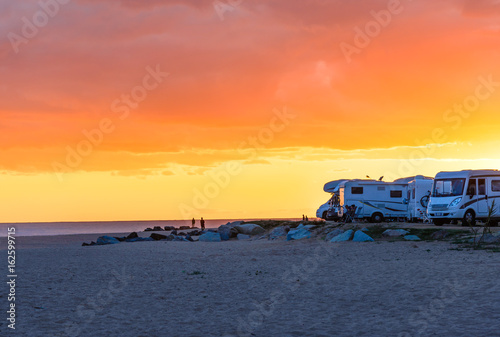 Motor homes, camper vans at sunset beach.Travel adventure vacation.
