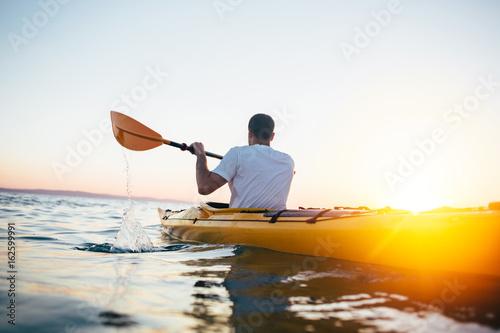 Man paddling the kayak at sunset