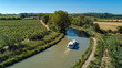 canvas print picture - Aerial top view of boat in Canal du Midi from above, family travel by barge and vacation in Southern France