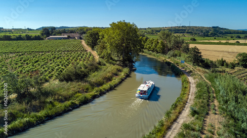 Fotografia Aerial top view of boat in Canal du Midi from above, family travel by barge and
