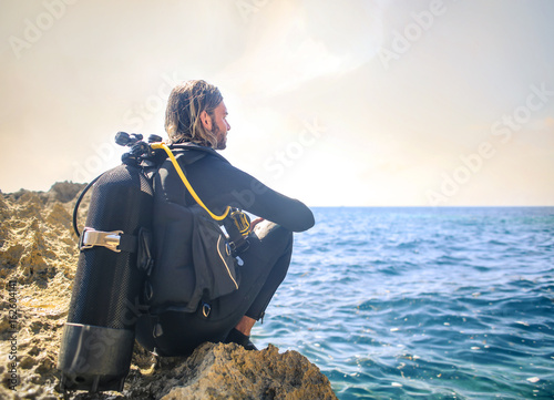 Spoed Fotobehang Duiken Scuba diver sitting on a rock, looking the sea
