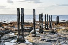Wooden Pillars On Rocks At Low...