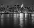 Manhattan skyline reflected in East River at night, New York City, USA.