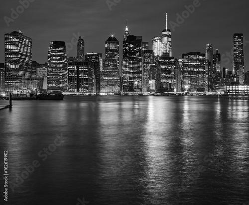 Fototapeta Manhattan linia horyzontu odbijał w Wschodniej rzece przy nocą, Miasto Nowy Jork, usa.