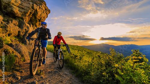 Valokuva Mountain biking women and man riding on bikes at sunset mountains forest landscape