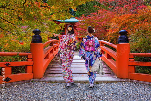 Poster Japan Women in kimonos walking at the colorful maple trees in autumn, Kyoto. Japan