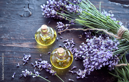 Valokuva  Fresh lavender with essential oil on rustic wood