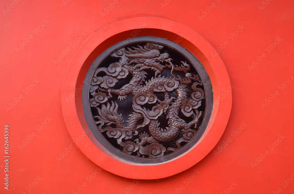 Wooden Carved dragon in circle on red background in Chinese Buddhism Temple in Lumbini, Nepal