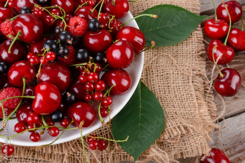 Poster Vruchten Mature berries on a plate on a wooden table