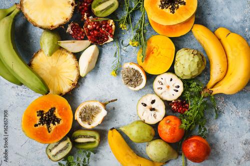 Tropical, exotic and citrus fruits arrangement. Papaya, cherimoya, mango, maracuja, banana, pineapple, pomegranate tropical fruits over blue table. Top view.