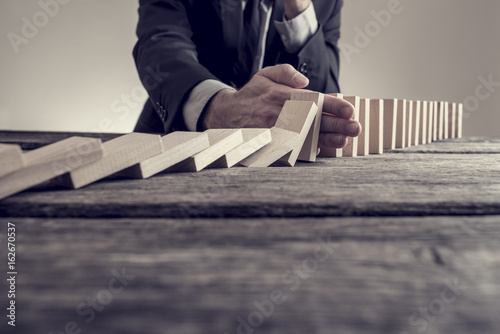 Fototapeta Toned image of a businessman stopping domino effect obraz