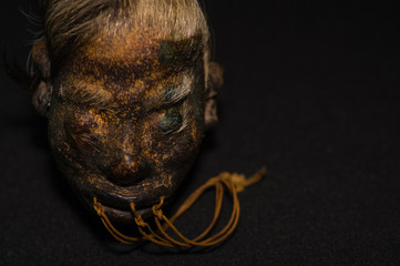 A shrunked human head from ecuador over a dark background