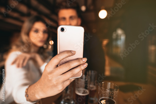 Fototapety, obrazy: Couple sitting in the bar and taking a selfie