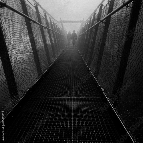 Fotografia  silhouettes walking on the bridge at Alps