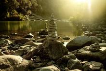 Cairn On A Peaceful Lake In The Sunset