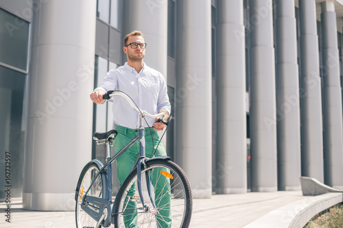 Fotografía  Cool young bearded hipster with bicycle on the city street