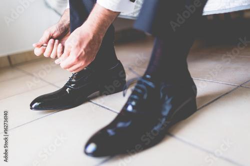 Uomo che si allaccia scarpe nere eleganti prima di un evento