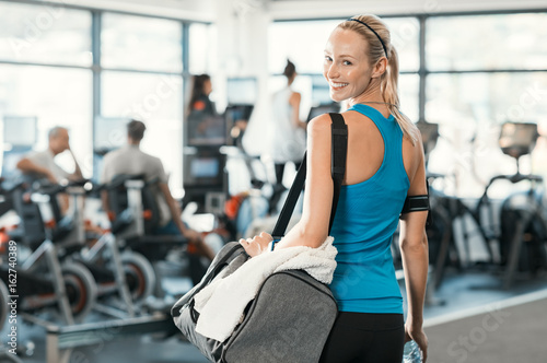 Photo Stands Fitness Woman with gym bag