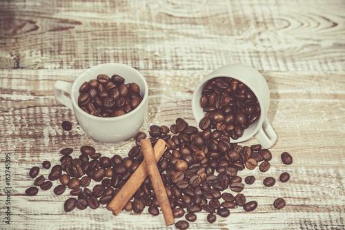 dwie-filizanki-kawy-z-ziarenkami-i-laskami-cynamonu-na-stole