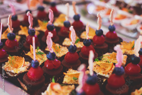 Poster Confiserie Decorated catering banquet table with different food appetizers assortment on a party