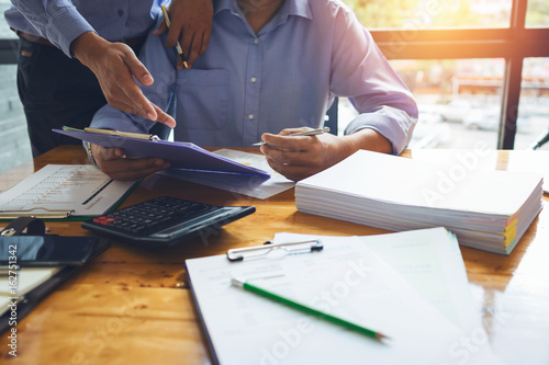 Fototapeta Business man accountant working hard with accounting financial report of annual 2017 with tax paperwork or job order product. obraz
