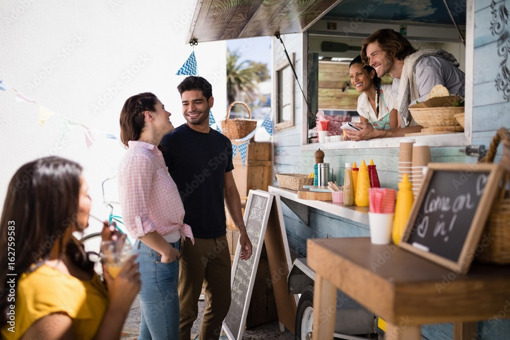 Fototapety, obrazy: Couple interacting with each other at food truck van