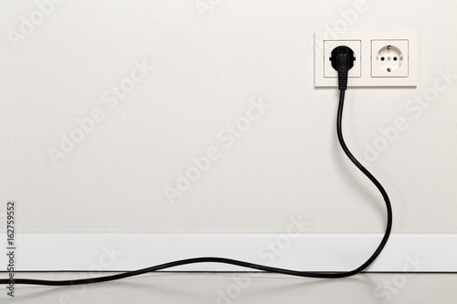 Leinwand Poster Black power cord cable plugged into european wall outlet on white plaster wall
