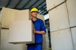 Worker holding a cardboard boxes while walking