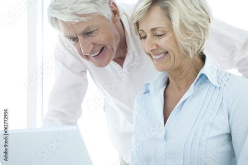 Plakat Szczęśliwa para na emeryturze senior przy użyciu laptopa ze sobą