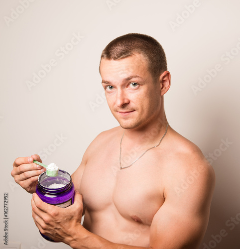 Fotografia  young man eats with cans protein