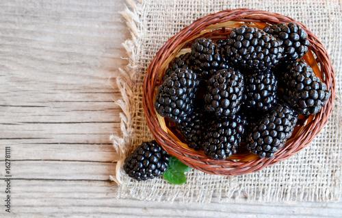 Fotografija  Ripe blackberries in a basket on burlap cloth on old wooden background
