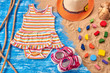 Baby Child summer stuff to the beach on a blue wooden background with rope and sand. Top view.