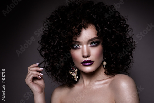 Plakat Piękna młoda kobieta z kręcone, małe i długie włosy. Włosy stałe. Seksowny dama, piękna dziewczyna na szarym tle. Portret. Falowane włosy, idealny makijaż. Zamknięte oczy.