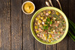 Okroshka. Traditional Russian summer cold soup with sausage, vegetables and kvass in bowl on wooden background.