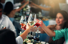 Closeup Photo Of Hands Clinking Glasses With Wine At Party.
