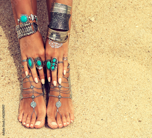 Poster Pedicure Woman In Relaxation On Tropical Beach with sand , body parts . Tanned girl leg with silver jewelry,bracelets and rings with turquoise.Boho style feet and hands