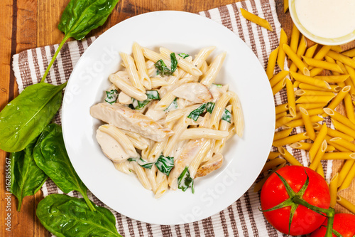 Photo Chicken Alfredo Pasta with Spinach. Selective focus.