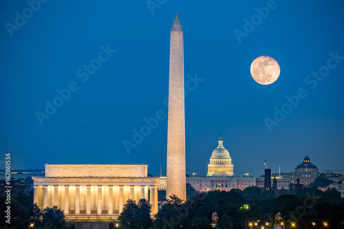 Photo Stands Historical buildings Supermoon above three iconic monuments: Lincoln Memorial, Washington Monument and Capitol Building in Washington DC as viewed from Arlington, Virginia
