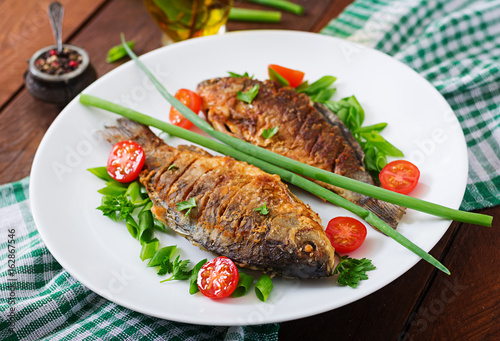 Poster Fish Fried fish carp and fresh vegetable salad on wooden background.