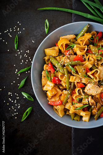Photo  Stir Fry from chicken fillet, green beans and paprika with pasta in the form of heart