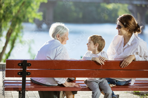 Senior woman, her adult granddaughter and great grandson in park Canvas Print