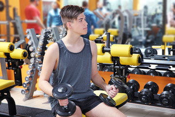 Guy training with dumbbells in modern gym