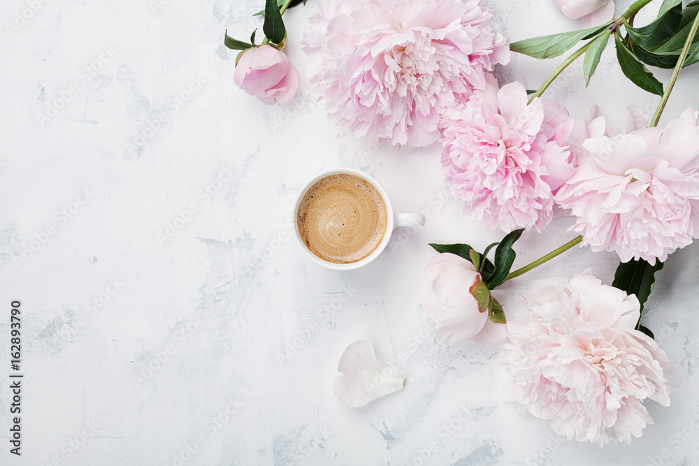 Morning coffee and beautiful pink peony flowers on white stone table top view in flat lay style. Cozy breakfast on Mother or Woman day.