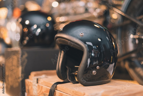 Black glossy vintage helmet place on the wooden box in selective focus with vintage tone.