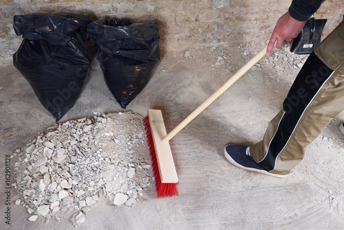 Fotografía  Workman sweeping the rubble with broom