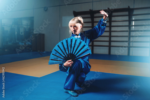 Fotografering  Female wushu master with fan, martial arts